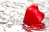 Red heart on foil — Stockfoto