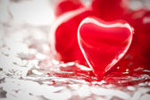 Red hearts on metal foil — Stock Photo