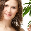 Closeup portrait of woman touching green plant - Stock Photo