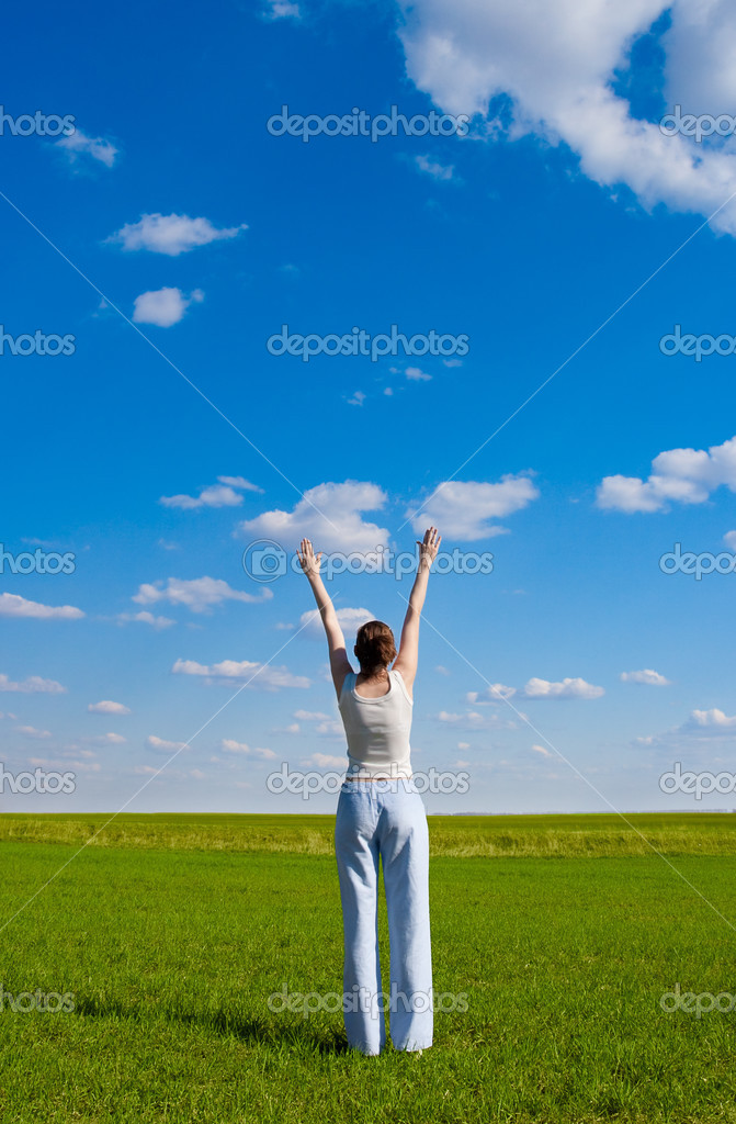 Woman rising up hands on green meadow over the blue sky — Stock Photo #3450748