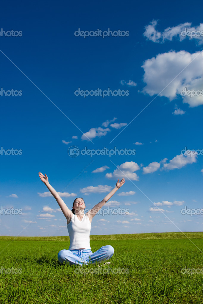 Woman sitting on green grass and rising up her hands  Stock Photo #3450824
