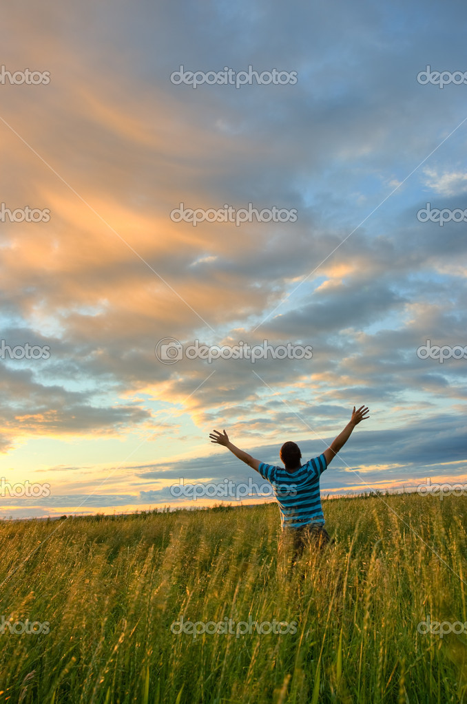 Young man rising hands over sunset  Stock Photo #3451213