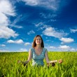 Woman meditating on field — Stockfoto