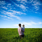 Father and son on green field — Stock Photo