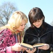Two girls read the book in a park — Stock Photo