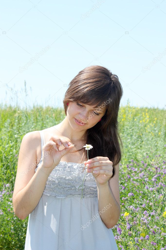 The young girl guesses on a camomile flower — Stock Photo #3387819