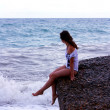 The girl sits on seacoast — Stock Photo