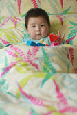 Lovely chinese baby in bed — Stock Photo