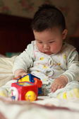 Chinese baby playing toys — Stock Photo