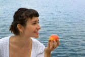 Young girl with the peach — Stock Photo
