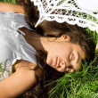 Pretty girl in white sleeping on the grass — Stock Photo