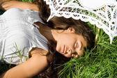 Söt flicka i vit sovande på gräset — Stockfoto