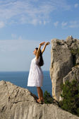 Happy young girl standing on the rocks — Stock Photo