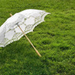 White elegant umbrella on fresh grass — Stock Photo