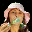 Portrait of a funny young girl blowing bubbles — Stock Photo