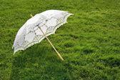 Taze çimenlerin üzerinde beyaz şık şemsiye — Stok fotoğraf