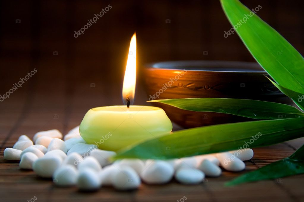 Composition with white zen stones, burning candle, bamboo leaves and clay bowl with tea symbolizing harmony, calmness and relaxation  Stock Photo #3898633