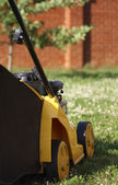 Yellow lawn mower on green grass — Stock Photo