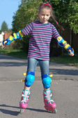Girl riding on roller blades on summer holidays — Stock Photo