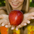A girl shows a red apple — Stock Photo #3516343