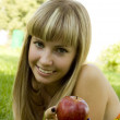 The girl with red apple outdoors — Stock Photo