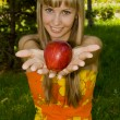 A girl shows a red apple — Stock Photo