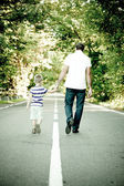 Father with his son go away hand to hand — Stock Photo