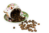 Coffee cup with scattering of coffee beans. Isolated on a white — Stock Photo