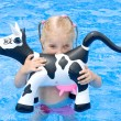 Happy small girl in a pool with toy cow — Stock Photo