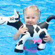 Happy small girl in a pool with toy cow — Stock Photo #3440512