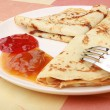 Pancakes with delicious jam on white plate - Stock Photo