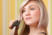 Young adult woman holding straightener — Stock Photo
