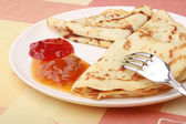Pancakes with delicious jam on white plate — Stock Photo