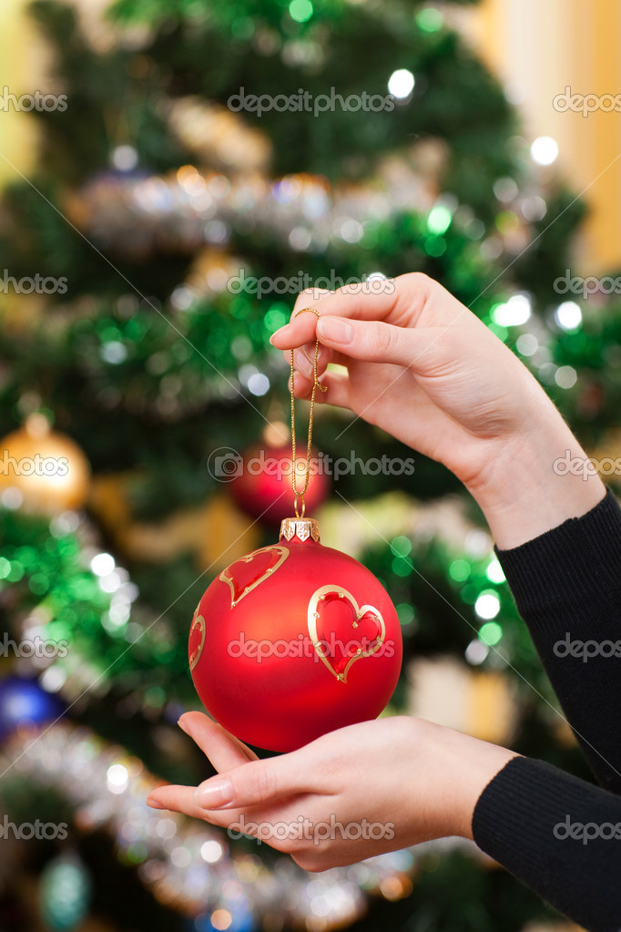 Beautiful female hands holding christmas toy on a background of christmas tree — Stock Photo #3405141