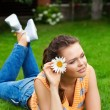 Girl with flower on grass — Stock Photo