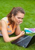Girl with laptop on grass — Stock Photo