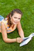 Girl with book on grass — Stock Photo