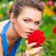 Lady with rose in garden - Stock Photo