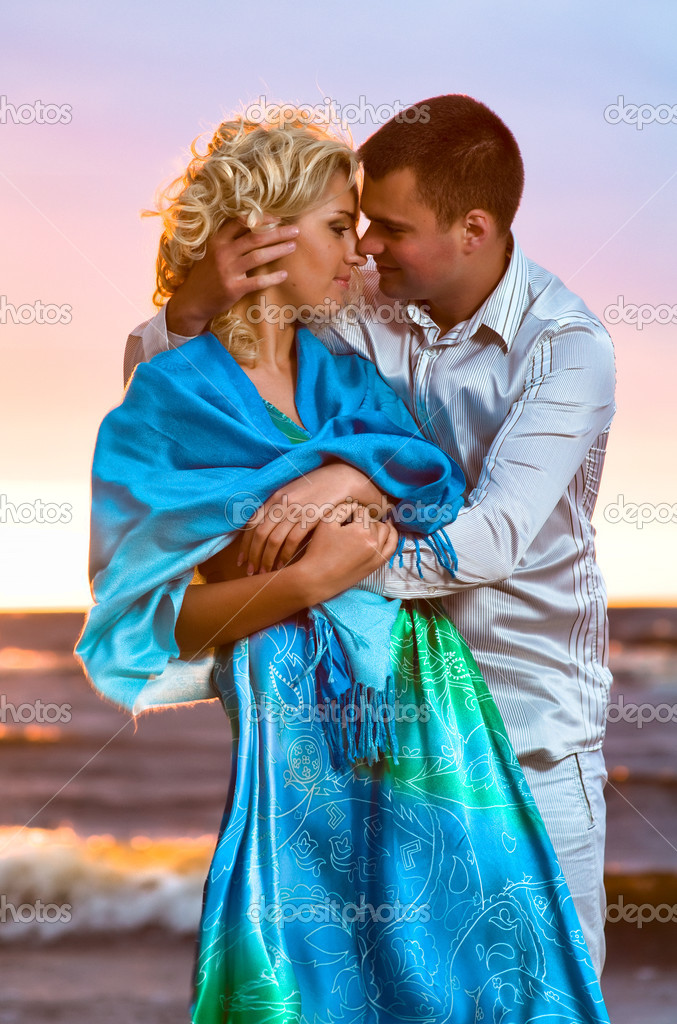Young couple in love near the sea at sunset — Stock Photo #3476441