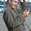 Happy man with mobile phone outdoors — Stock Photo