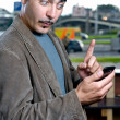 Funny portrait of a man with mobile phone outdoors - Stock Photo