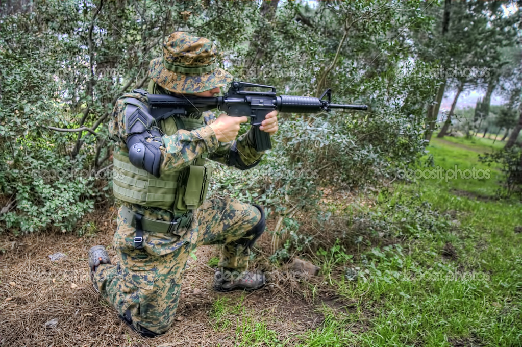 A soldier wearing camouflage cloth is directing an air gun to shoot — Stock Photo #3809955