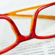 Stock Photo: Reading glasses on book