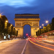 Arc De Triomphe and light trails - Stock Photo
