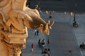 Gargoyle of Notre Dame looking down the street — Stock Photo