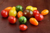 Fresh wet tomatoes on wooden table — Stock Photo
