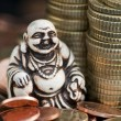 Laughing Budda in front of coins — Stock Photo