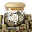 A jar full of coins on white background — Stock Photo