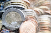 Shiny euro coins frozen in ice with german coin in front — Stock Photo