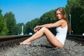 Young woman sits on railway rails — Stock Photo